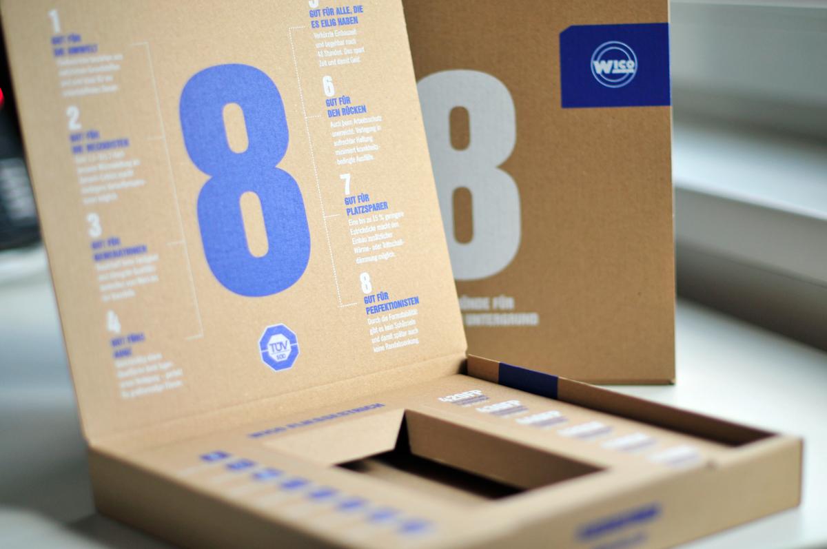 Kartonbox aus Wellpappe zur Verpackung eines WICO Fließestrich Musters. Ansicht von vorne.
